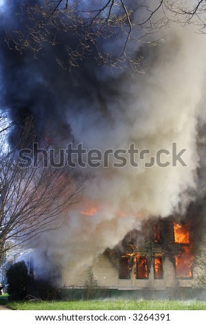 House on fire with smoke billowing from it - stock photo