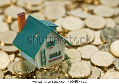 house on gold coins closeup - stock photo