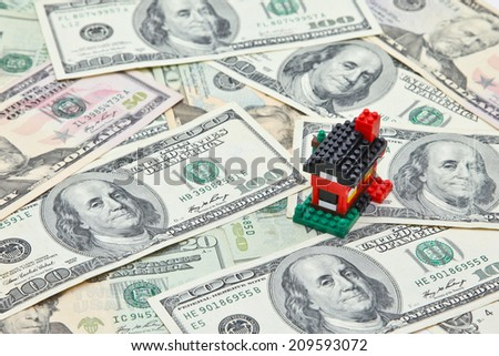 House on pile of US dollar banknotes - stock photo