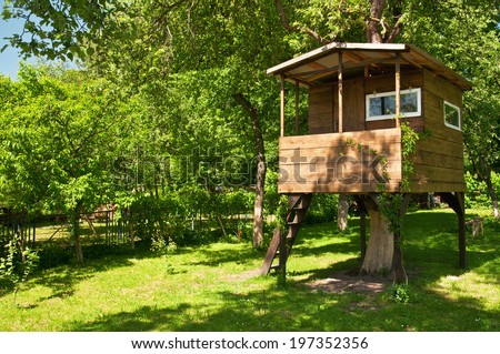 house on tree in evening garden  - stock photo