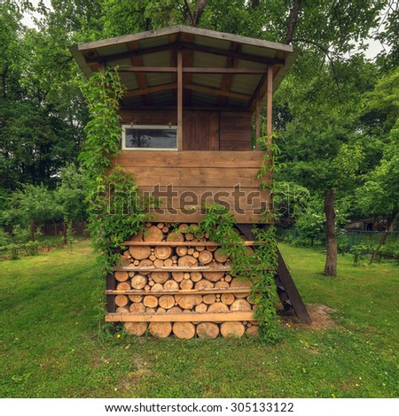 house on tree in summer garden - stock photo