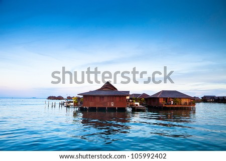 house over water at coastline with sunset