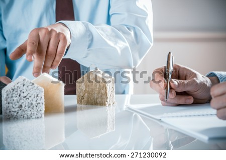 House owner and architect discussing a choice of insulation materials pointing to one as the architect draws up the contract - stock photo