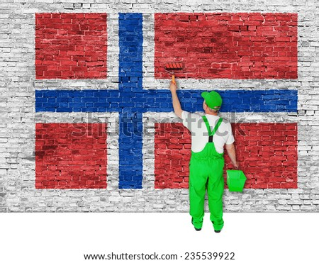 house painter covers brick wall with flag of Norway - stock photo