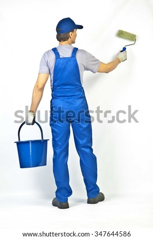 house painter is painting white wall, Back view from behind Young full length man in blue overalls with painting tools Empty copy space for inscription - stock photo