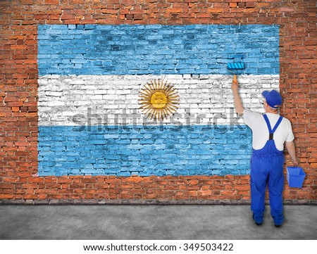 House painter paints flag of Argentina on old brick wall - stock photo