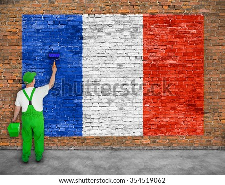 House painter paints flag of France on old brick wall