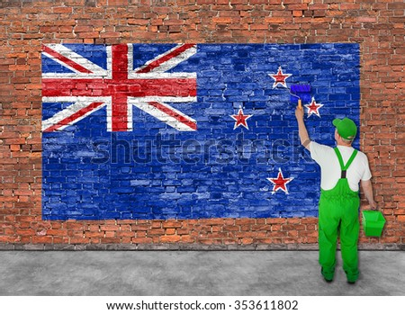 House painter paints flag of New Zeland on old brick wall - stock photo