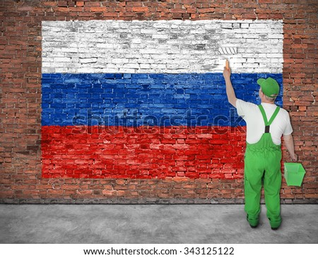 House painter paints flag of Russia on old brick wall - stock photo