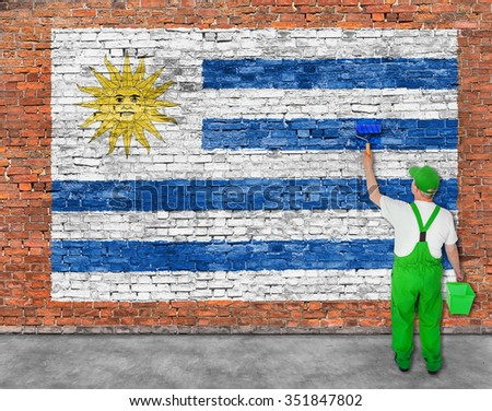 House painter paints flag of Uruguay on old brick wall - stock photo