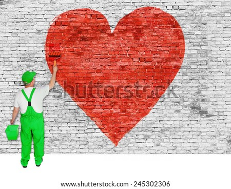 House painter paints symbol of broken love on white brick wall - stock photo
