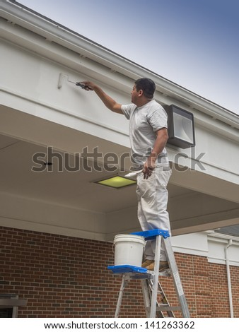 House painter rolling new paint on soffit - stock photo