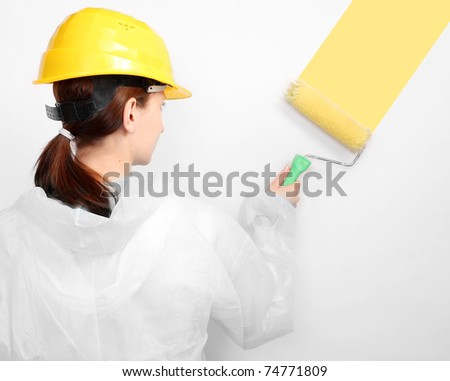 House painter with roller applying of yellow pant on a white wall.