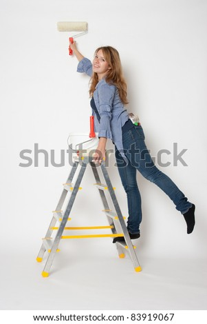 House painter woman standing on stepladder