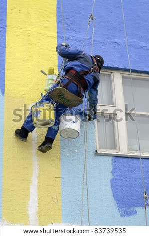 House painters paint the facade of building - stock photo