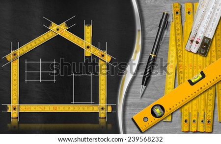 House project concept. Wooden meter ruler in the shape of house with a drawing, propelling pencil, two meter tools and spirit level on a blackboard and wooden background - stock photo