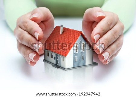 house protected of woman hands - protect and insurance real estate concept  - stock photo