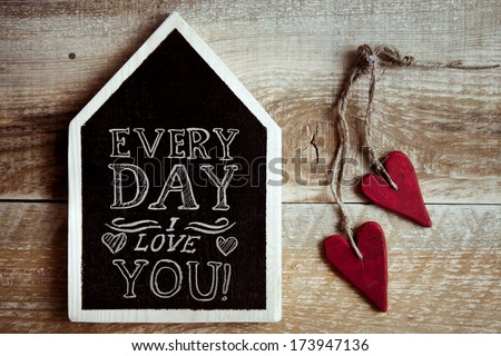 "house shaped chalk board  ""Every day I love you"" with two red vintage hearts and rustic old wooden background - stock photo"