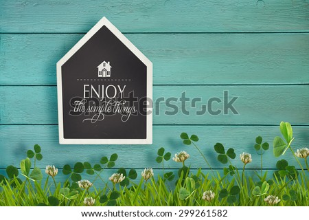 House shaped chalkboard and grass on wooden background - stock photo