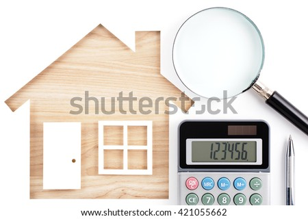 House shaped paper cutout, calculator, magnifier and pen on natural wood lumber. Isolated on white background.  - stock photo