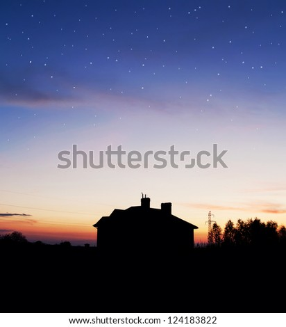 House silhouette with gorgeous sunset sky and stars background - stock photo