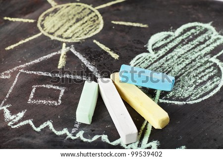 House, sun and tree drawing and chalks on a blackboard - stock photo