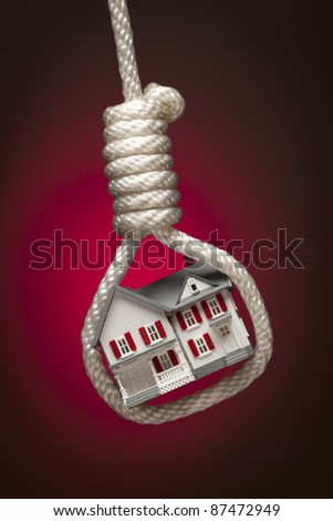 House Tied Up and Hanging in Hangman's Noose on Red Spot Lit Background. - stock photo