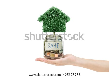 house tree with saving money. Money concept.money on hand. Hand holding glass of money saving money.save money for buy the house.save money for family. money in glass  - stock photo