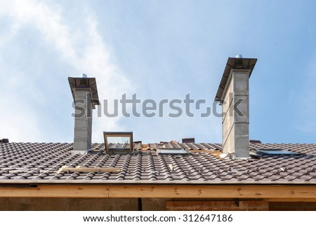 House under construction. Roofing tiles installation. New roof with skylight and chimneys - stock photo