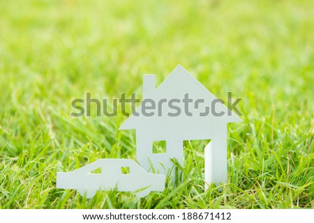 House white paper cut concept in green field background