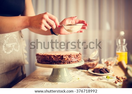 House wife wearing apron making finishing touches on birthday dessert chocolate cake.Woman making homemade cake with easy recipe,sprinkling  powdered sugar on top.Icing sugar sprinkled with colander - stock photo