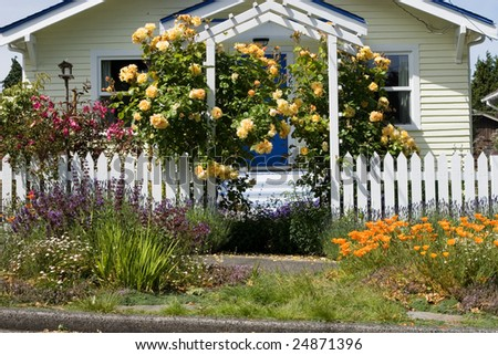 house with bright flowers in the front yard - stock photo