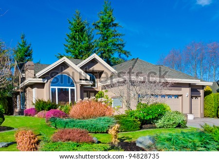 House with colorful front yard and blue sky  in a sunny  day' - stock photo