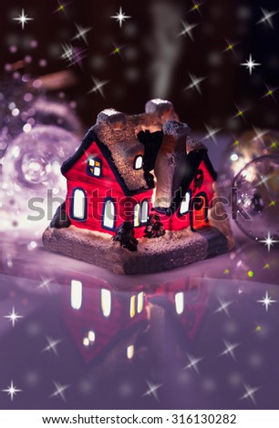 House with glowing windows, Christmas card - stock photo