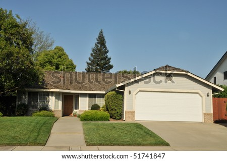 House with landscaping and sky on a sunny day.