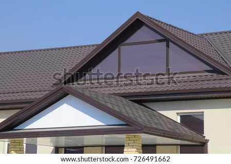 House with plastic windows and a brown roof of corrugated sheet. Roofing of metal profile wavy shape on the house with plastic windows.