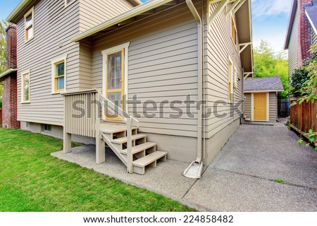 House with small deck and concrete walkways. Backyard view - stock photo