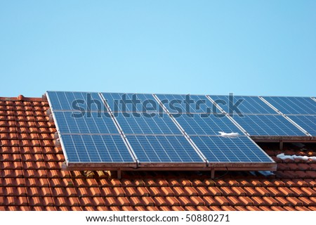house with solar panels and blue sky in the background - stock photo