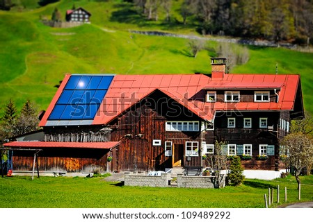 House with solar panels in the green mountain valley near forest - stock photo
