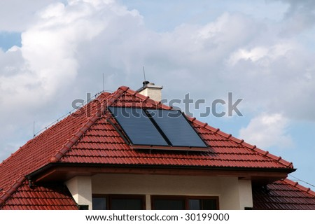 House with solar panels on the roof for water heating. - stock photo