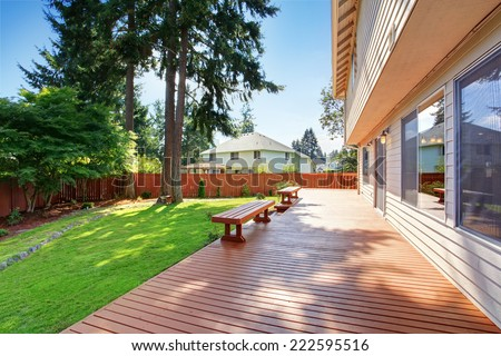 House with spacious wooden walkout deck and benches - stock photo
