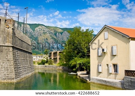 House with tile roof, canal and fortress wall in the city of Kotor, in Montenegro - stock photo