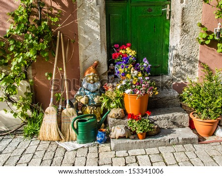 House with watering can, garden gnome, brooms and pots with plants. - stock photo