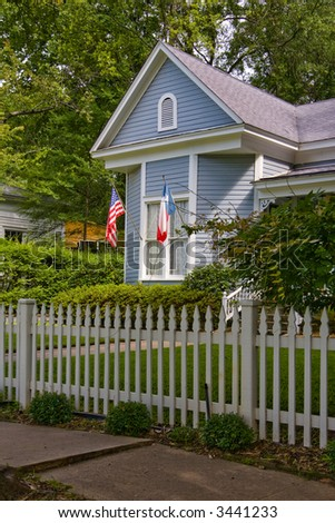 House with white picket fence and American and Texas flags - stock photo