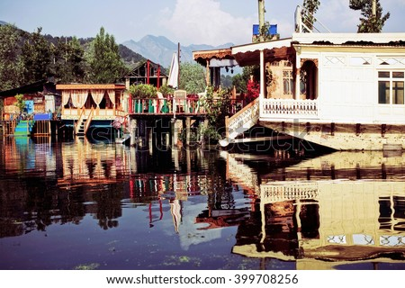 Houseboats on the lake in Srinagar against the mountains. India