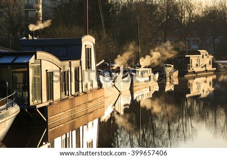 Houseboats with smoke from their chimneys on a clod spring day in a Dutch canal, Groningen. - stock photo