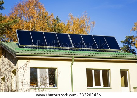 household with solar panels on the roof - stock photo