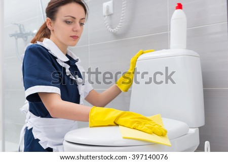 Housekeeper or maid in a neat uniform cleaning a white bathroom kneeling down wiping the toilet with a yellow cloth with gloved hands