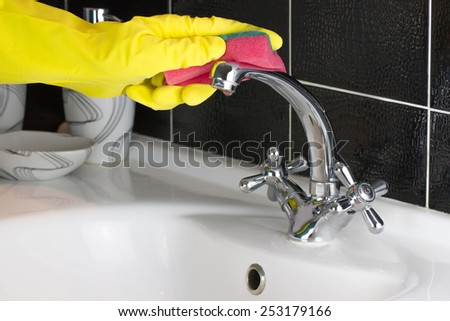 Housekeeping concept. Hand in protective glove washing cleaning tap with rag at bathroom - stock photo