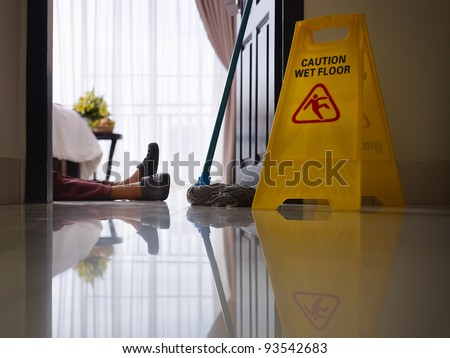 housemaid had accident at work while cleaning floor in hotel room. Side view, low angle - stock photo